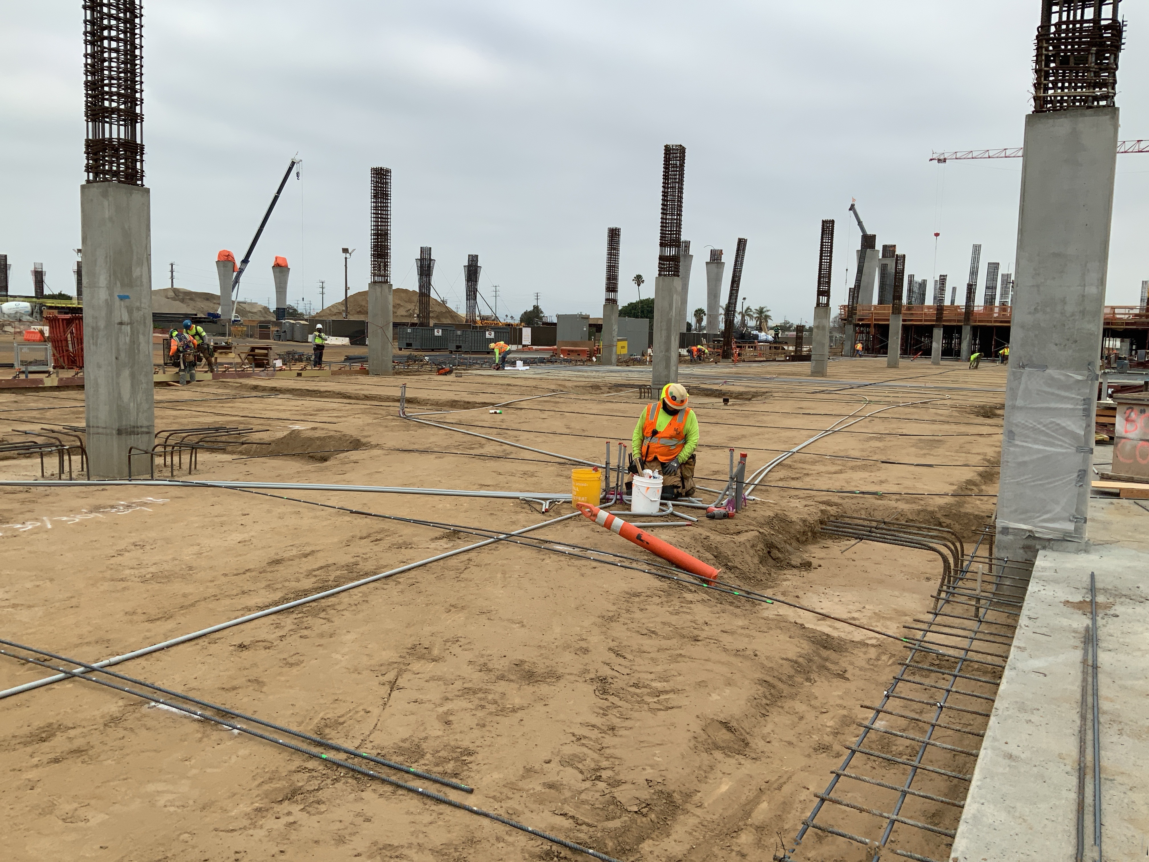 Electrician and rebar crew installation prior to slab on grade pour at the Consolidated Rent-A-Car facility Ready Return/Idle Storage building.