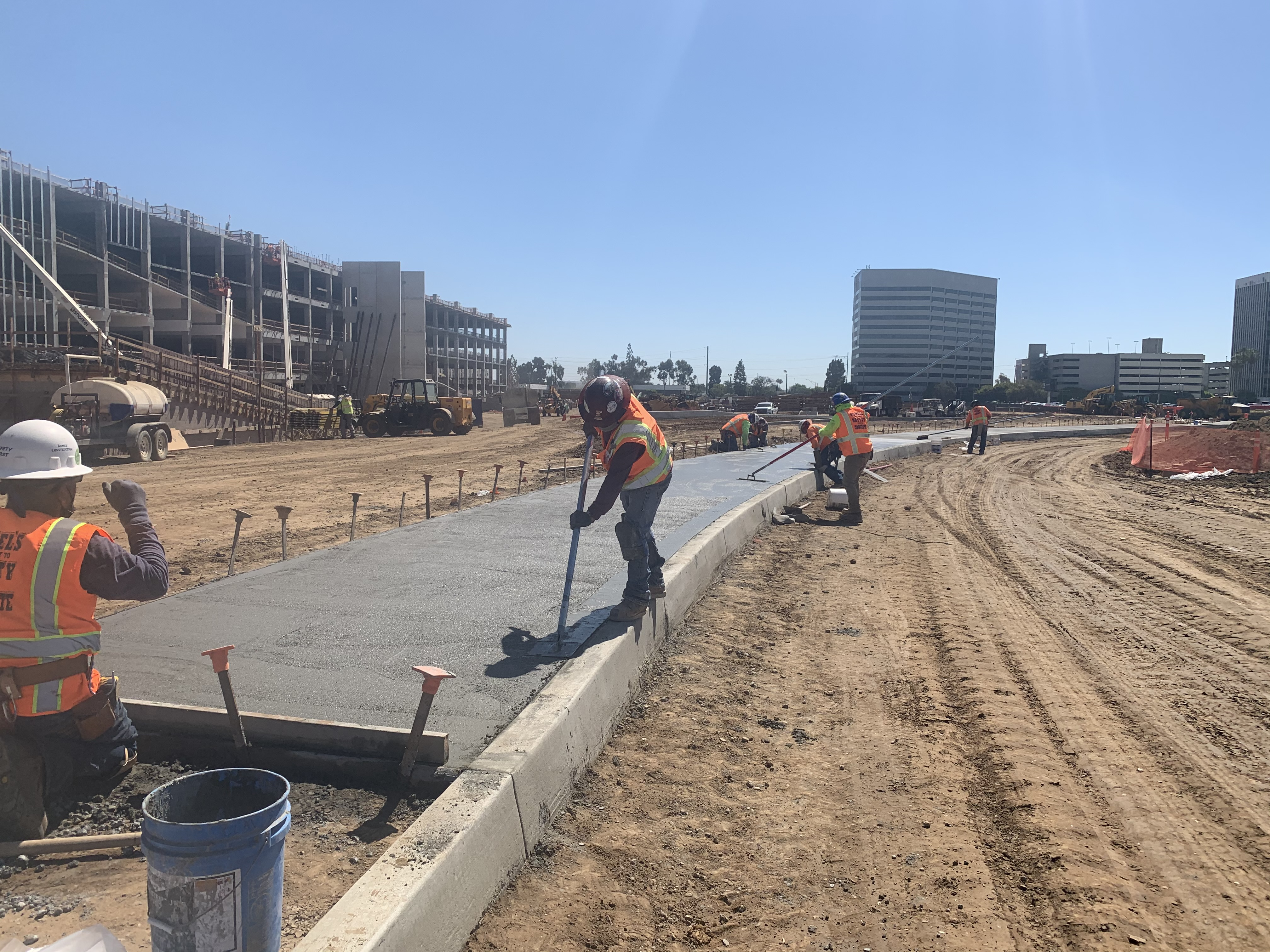Workers smoothing concrete at the Consolidated Rent-A-Car facility.
