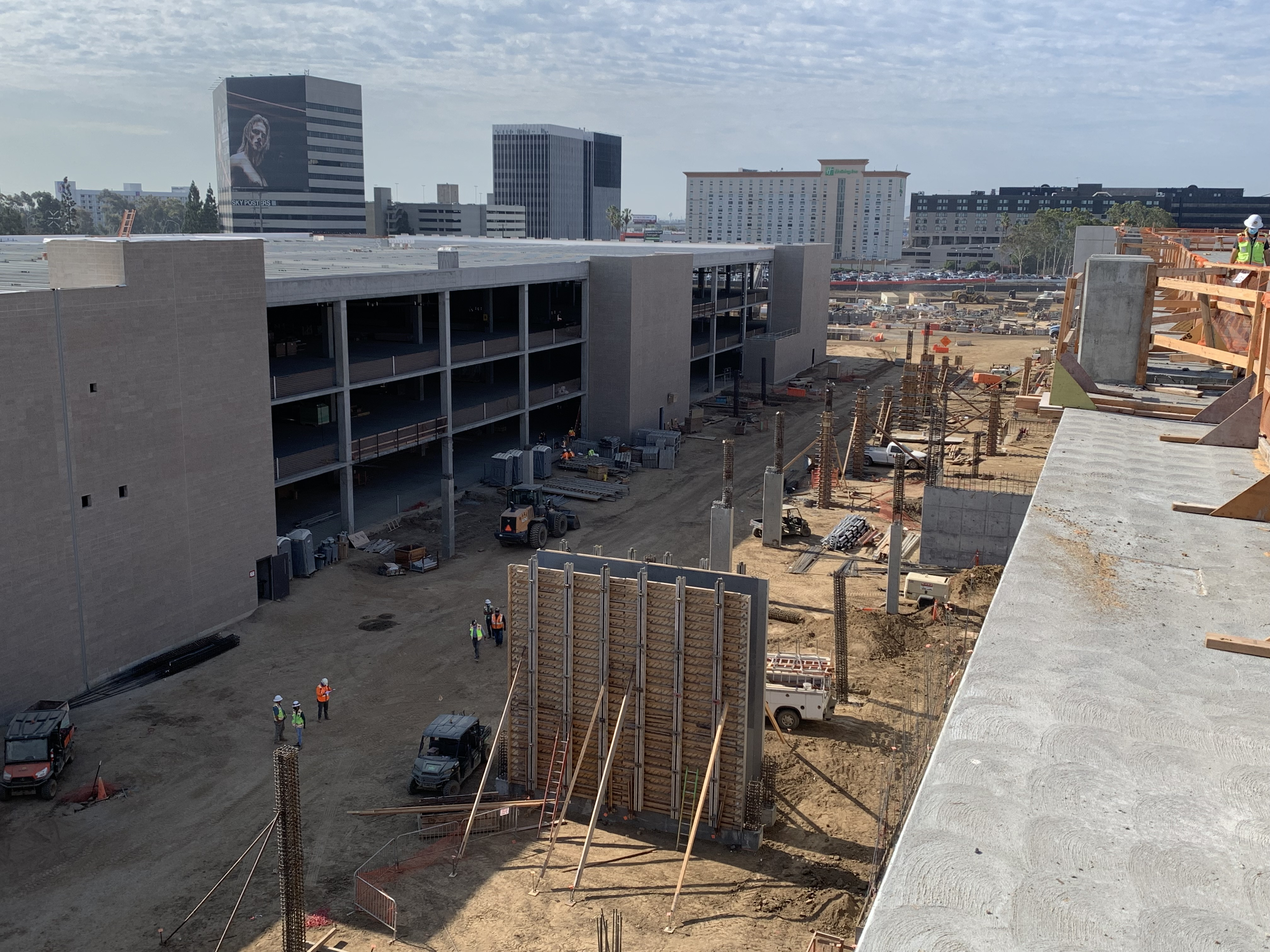 Forming and stripping of columns and shear walls for the connecting bridges and ramps at the Consolidated Rent-A-Car facility in the area between the Idle Storage and Quick Turn Around buildings.